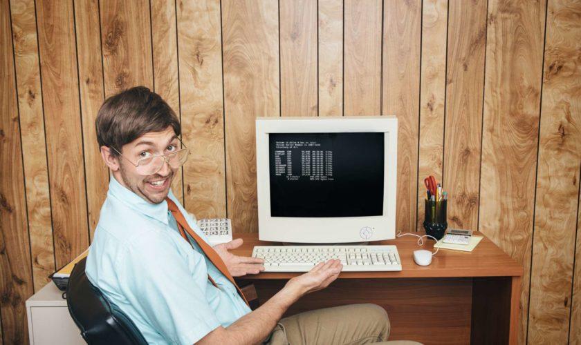 Büroangestellter sitzt vor seinem PC - Bürojob in der Vergangenheit - Computer - Humor