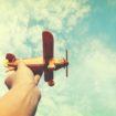 Kinderhand hält Spielzeugflugzeug in die Luft - Innovation